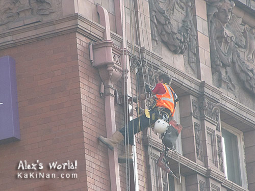 Man belayed to paint the building's pipe